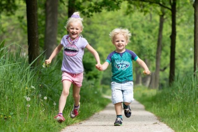 Marleen Verheul Fotografie, kinderfotografie, broer en zus rennen door het park