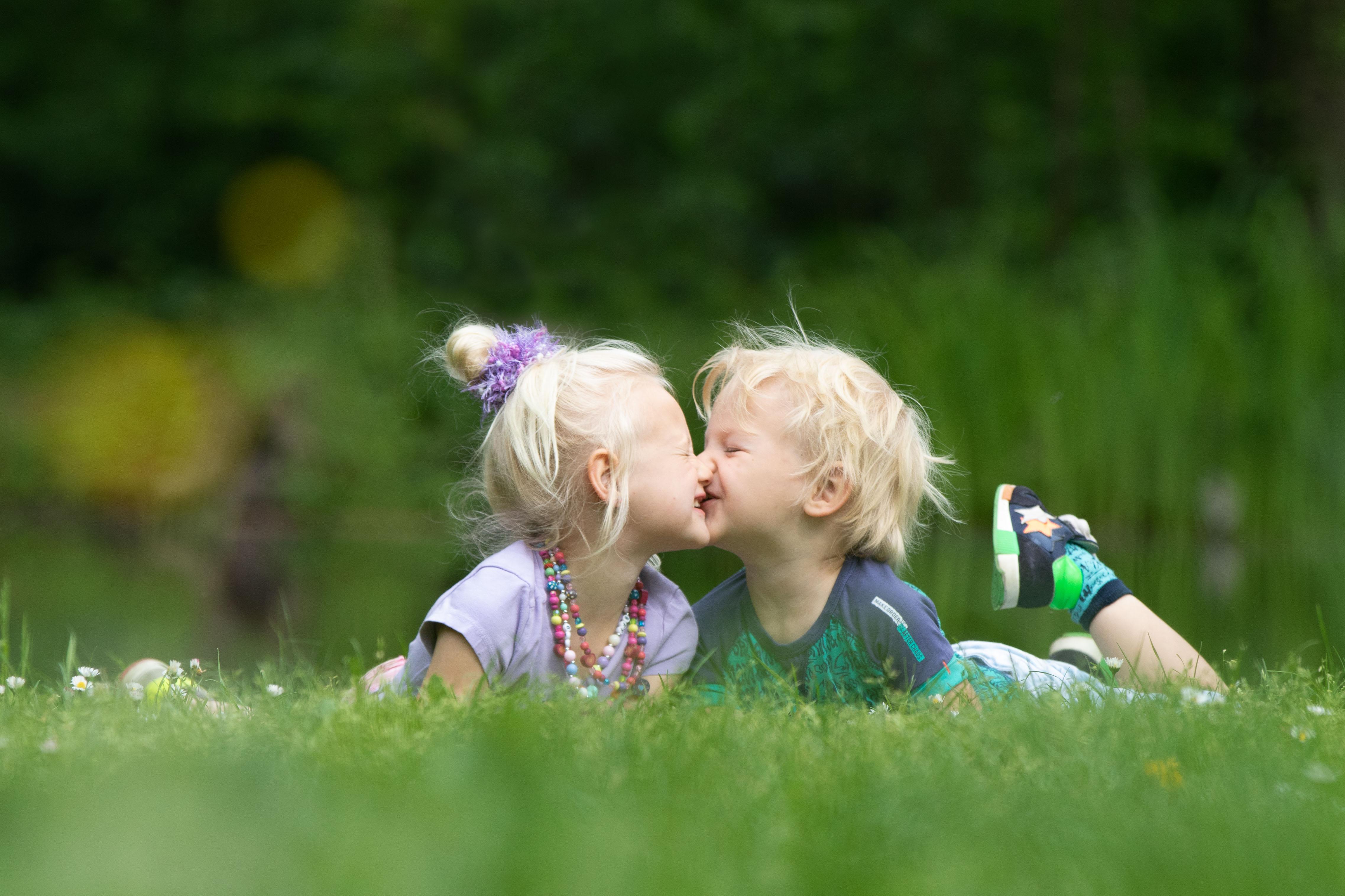 Marleen Verheul Fotografie, kinderfotografie, broer en zus geven elkaar een kus in het gras