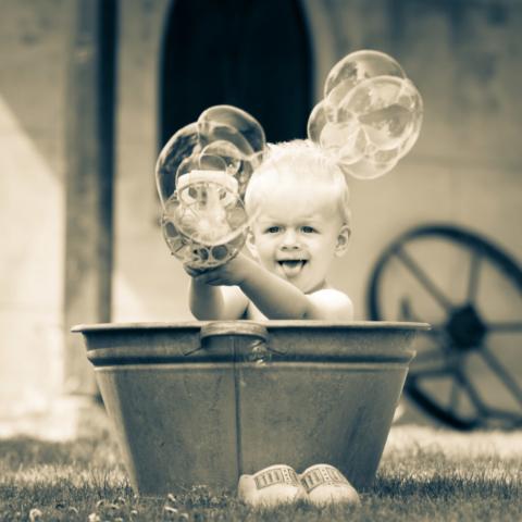 Marleen Verheul Fotografie, kinderfotografie, jongetje met bellenblaas in ouderwetse zinken teil