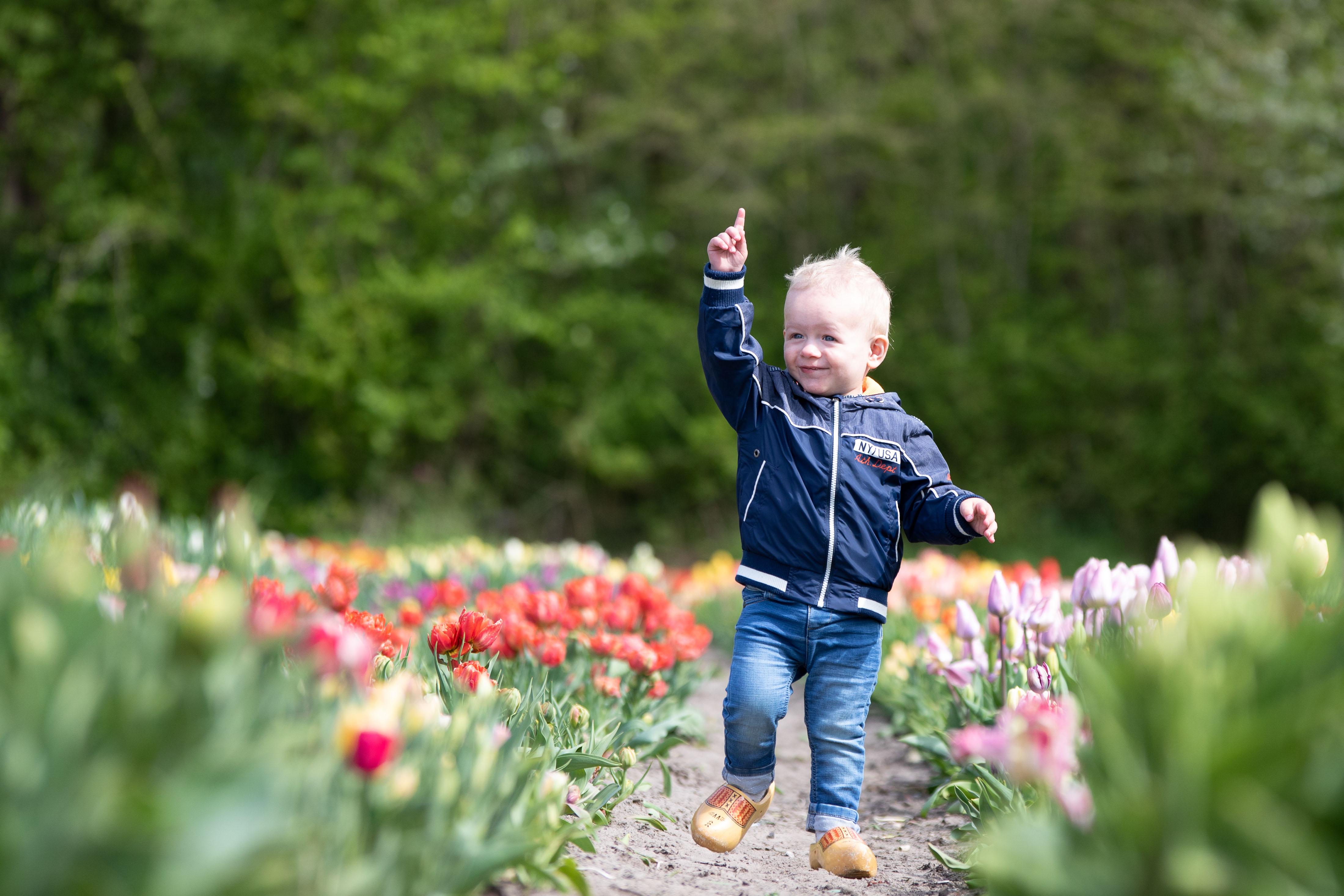 Marleen Verheul Fotografie, kinderfotografie, jongetje met klompen tussen de tulpen